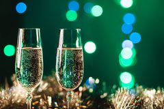 Vidrios con champán contra los fuegos artificiales y las luces del día de fiesta - Ce Imagen de archivo
