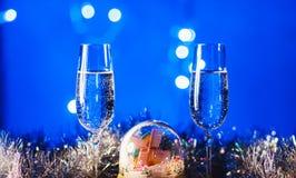 Vidrios con champán contra los fuegos artificiales y las luces del día de fiesta - Ce Imagen de archivo libre de regalías