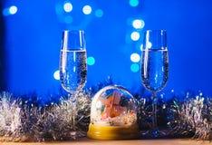 Vidrios con champán contra los fuegos artificiales y las luces del día de fiesta - Ce Foto de archivo
