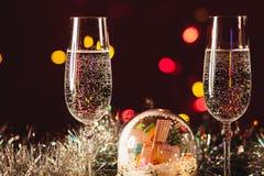 Vidrios con champán contra los fuegos artificiales y las luces del día de fiesta - Ce Fotos de archivo