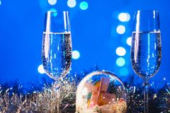 Vidrios con champán contra los fuegos artificiales y las luces del día de fiesta - Ce Foto de archivo libre de regalías