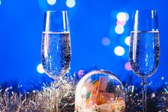 Vidrios con champán contra los fuegos artificiales y las luces del día de fiesta - Ce Imágenes de archivo libres de regalías