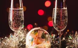 Vidrios con champán contra los fuegos artificiales y las luces del día de fiesta - Ce Fotografía de archivo libre de regalías