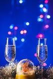 Vidrios con champán contra los fuegos artificiales y las luces del día de fiesta - Ce Fotos de archivo libres de regalías