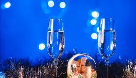 Vidrios con champán contra los fuegos artificiales y las luces del día de fiesta - Ce Fotografía de archivo