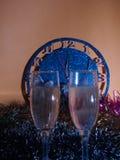 Vidrios con champán en el fondo del reloj El reloj Fotos de archivo libres de regalías
