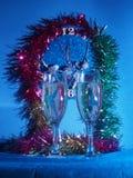 Vidrios con champán en el fondo del reloj El reloj Fotografía de archivo libre de regalías