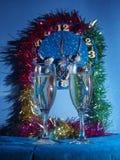 Vidrios con champán en el fondo del reloj El reloj Imagenes de archivo
