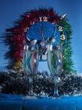 Vidrios con champán en el fondo del reloj El reloj Imagen de archivo libre de regalías