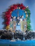 Vidrios con champán en el fondo del reloj El reloj Fotografía de archivo