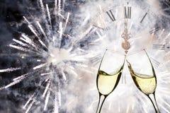 Vidrios con champán y el reloj cerca de la medianoche Imágenes de archivo libres de regalías