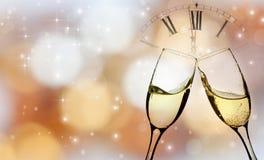 Vidrios con champán y el reloj cerca de la medianoche Fotos de archivo
