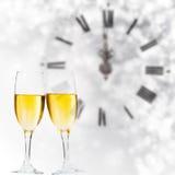 Vidrios con champán y el reloj cerca de la medianoche Foto de archivo libre de regalías