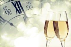Vidrios con champán y el reloj cerca de la medianoche Imagen de archivo libre de regalías