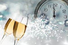 Vidrios con champán y el reloj cerca de la medianoche Imagenes de archivo