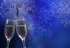 Vidrios con champán y el reloj cerca de la medianoche Imagen de archivo