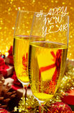 Vidrios con champán y la Feliz Año Nuevo de la frase Imagen de archivo libre de regalías