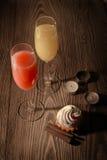 2 vidrios con el jugo y el helado en un fondo de madera con las velas Imagen de archivo