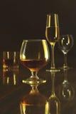 Vidrios con el vino blanco, rojo y el coñac o el whisky en la tabla del espejo Composición de las celebridades Imagen de archivo libre de regalías