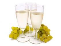 Vidrios con el vino blanco y la uva blanca Fotos de archivo