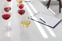 Vidrios con el vino delicioso en la tabla dentro Fotos de archivo libres de regalías