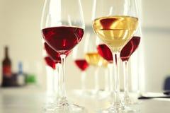 Vidrios con el vino delicioso en la tabla dentro Fotografía de archivo libre de regalías