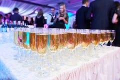Vidrios con el vino espumoso blanco en fila en el evento del restaurante Fotos de archivo libres de regalías