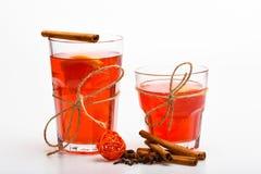 Vidrios con el vino reflexionado sobre o la bebida caliente atada con la secuencia de la guita en el fondo blanco, cierre para ar Imagen de archivo libre de regalías