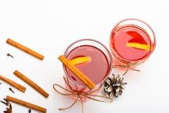 Vidrios con el vino reflexionado sobre o la bebida caliente atada con la secuencia de la guita en el fondo blanco, cierre para ar Imagenes de archivo