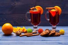 Vidrios con el vino reflexionado sobre o la sidra caliente cerca de rebanadas anaranjadas y galletas en fondo azul marino Vino re Fotografía de archivo libre de regalías