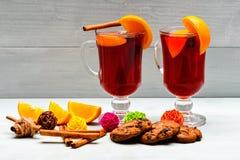 Vidrios con el vino reflexionado sobre o la sidra caliente cerca de rebanadas anaranjadas y galletas en el fondo blanco Vino refl Fotografía de archivo