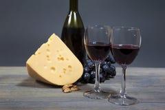 Vidrios con el vino rojo, el queso y un manojo de uvas en una tabla de madera Fotos de archivo libres de regalías