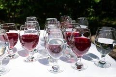 Vidrios con el vino rojo y un primer del agua antes del partido en café Fotografía de archivo