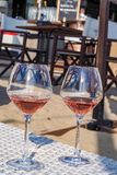 Vidrios con el vino rosado en una terraza arenosa fotos de archivo