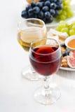 Vidrios con el vino y los bocados en la tabla blanca Fotos de archivo libres de regalías