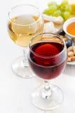 Vidrios con el vino y los bocados en la tabla blanca, primer Fotografía de archivo libre de regalías