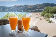 Vidrios con el zumo de naranja y el frappe en una tabla en la taberna griega tradicional Imagen de archivo
