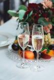 Vidrios con la bebida del champán en una tabla Consumición feliz de los recienes casados Los pares cariñosos crearon a la nueva f fotos de archivo