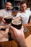 Vidrios con la cerveza que es sostenida por los amigos agradables felices imágenes de archivo libres de regalías