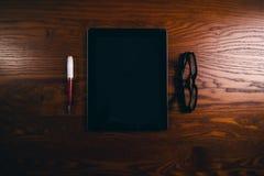 Vidrios con la pluma y la tableta en una tabla natural de madera Ministerio del Interior Concepto de trabajo en una oficina y acc Imagen de archivo