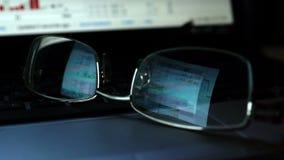 Vidrios con la reflexión de los datos de la compra y venta de acciones sobre un teclado del ordenador portátil metrajes