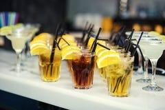 Vidrios con los cócteles, champán, jugo Vidrios en TA blanca Foto de archivo libre de regalías