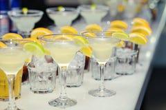 Vidrios con los cócteles, champán, jugo Vidrios en TA blanca Fotografía de archivo libre de regalías