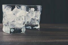 Vidrios con los cubos de hielo en fondo oscuro Fotografía de archivo