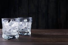 Vidrios con los cubos de hielo en fondo oscuro Imágenes de archivo libres de regalías