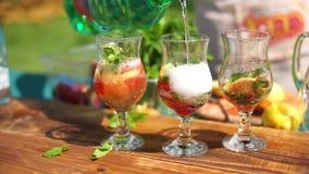 Vidrios con los ingredientes para la limonada, soporte en la tabla El camarero está volviendo a llenar el agua de soda almacen de video