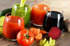 Vidrios con los jugos vegetales orgánicos frescos en la tabla de madera Foto de archivo libre de regalías