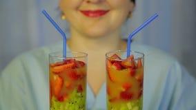 Vidrios con un cóctel del kiwi y de fresas frescos en las manos de un cocinero de la mujer almacen de video