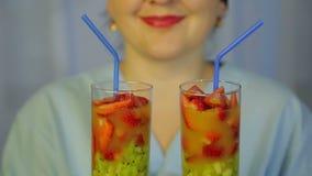 Vidrios con un c?ctel del kiwi y de fresas frescos en las manos de un cocinero de la mujer almacen de video