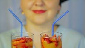 Vidrios con un c?ctel del kiwi y de fresas frescos en las manos de un cocinero de la mujer metrajes